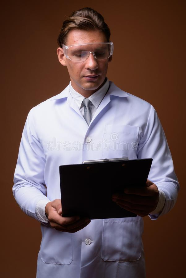 Man doctor wearing protective glasses against brown background stock photo