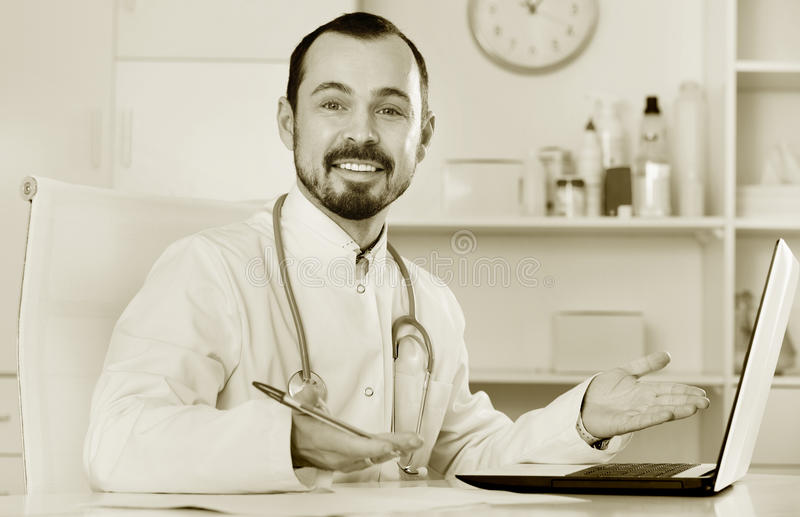 Man doctor working effectively in his office. Smiling man doctor working effectively in his office royalty free stock photo