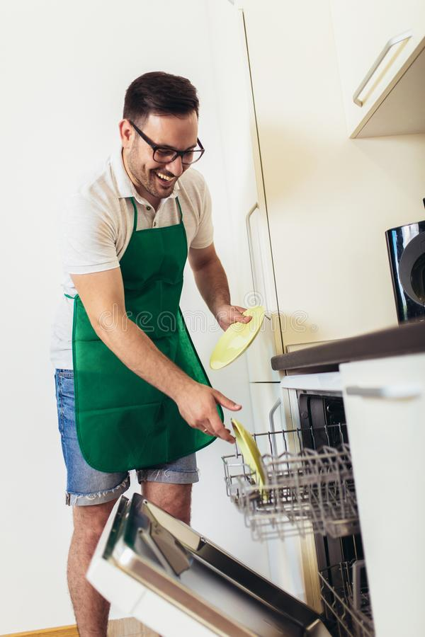 Man does housework in the kitchen royalty free stock photos