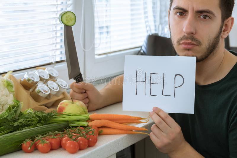 Man does not like to eat vegetables. He asks to help him stock image