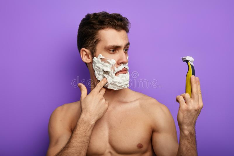 Man doesn`t expect that new shaver has many possitive effects. Close up photo.isolated on the blue background.surprise concept stock photo