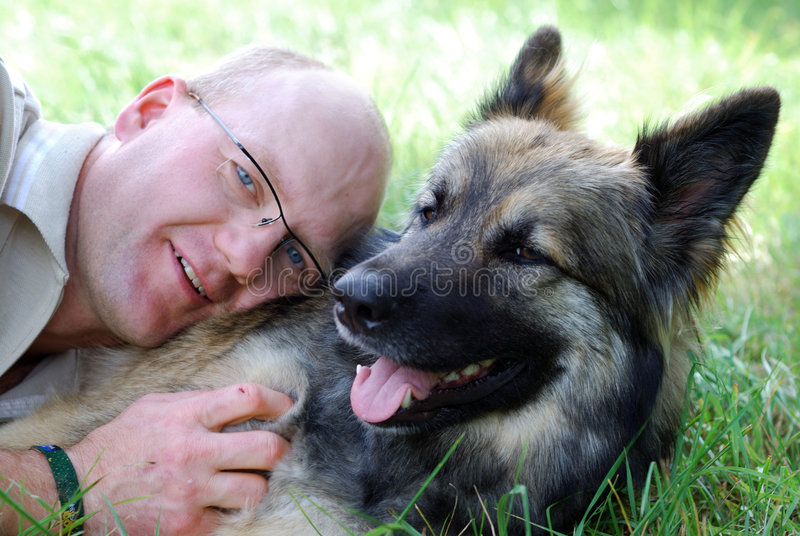 Man with dog. Man with his dog in summer lying on a meadow stock photography