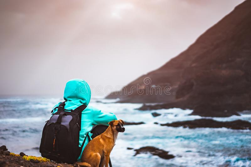 Man with a dog in front of rural coastline landscape with mountains and waves and sun rays comming through the clouds stock images