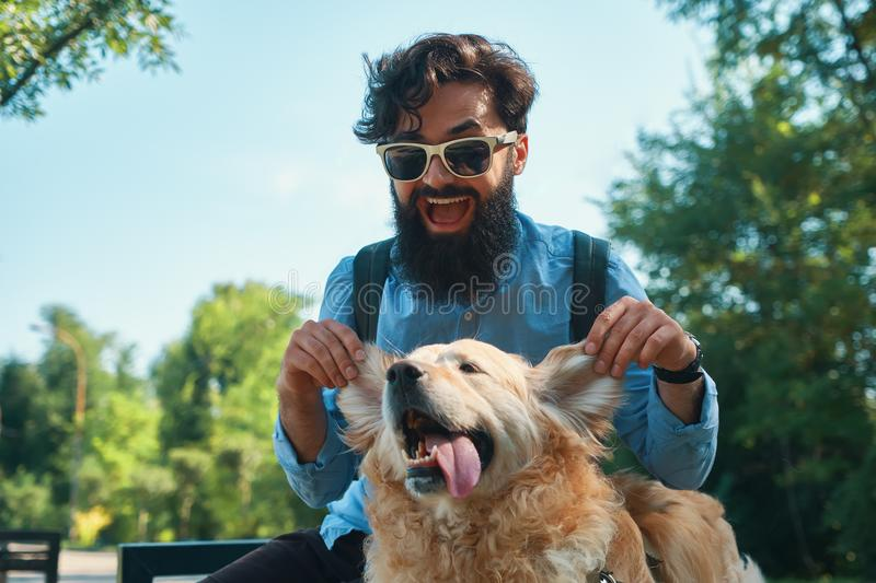 Man and dog having fun, playing, making funny faces while restin. G in the park. Life is beautiful, best friends concept stock image