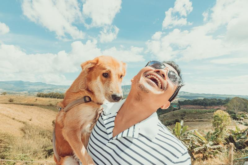 A man with  dog. mountain and blue sky and very nice clouds. A man with a dog. mountain and blue sky and very nice clouds stock photo