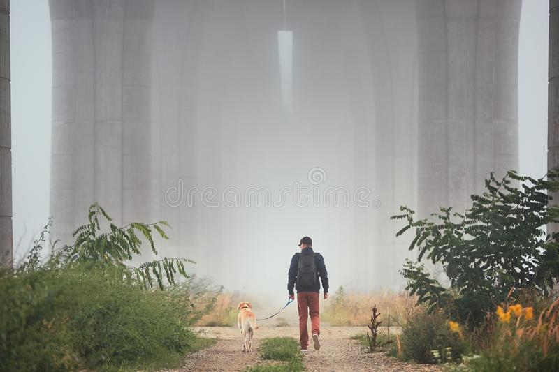 Man with dog in mysterious fog. Man with dog under highway bridge in mysterious morning fog. Prague, Czech Republic stock images