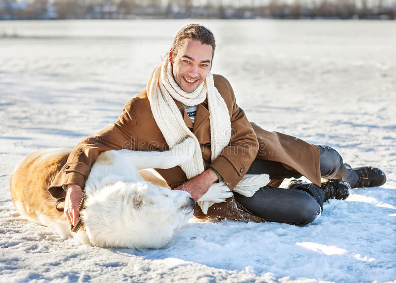 Man and dog outdoors. Man and central Asian shepherd playing with his dog outdoors stock photo