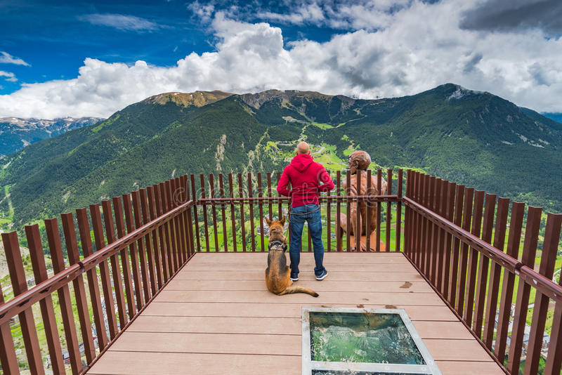 Man and dog overlooking at Andorra from observation deck. Man and dog overlooking at Andorra from observation deck Roc Del Quer royalty free stock image