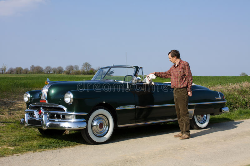 Man and dog in retro car royalty free stock photo