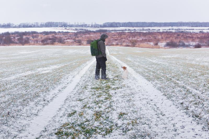 Man with dog on snowy road royalty free stock images