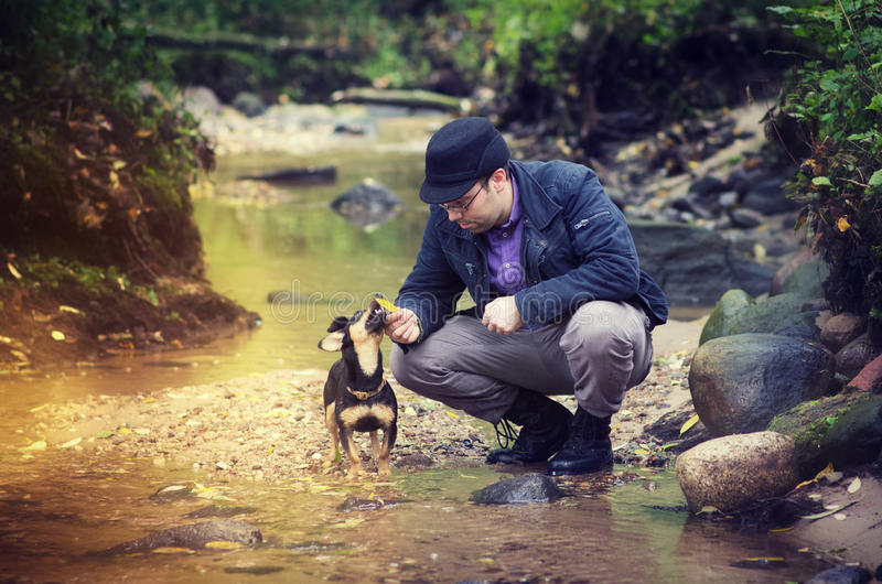 Man with dog at stream. A man and his dog playing near a stream stock photo