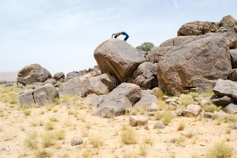 Man doing acrobatic movements on a rock. Man doing doing acrobatics on a big desert rock in a beautiful nature site royalty free stock photos