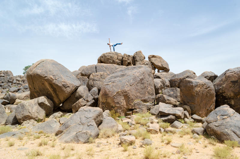 Man doing acrobatic movements on a rock #2. Man doing doing acrobatics on a big desert rock in a beautiful nature site royalty free stock photo