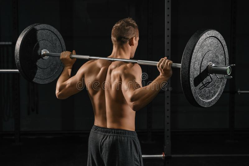 Man doing back squats exercise with a barbell. Crossfit training in a gym stock photo