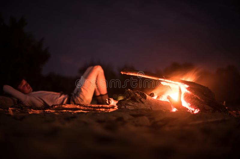 Man doing camping and lying on the beach near fire at night royalty free stock photos