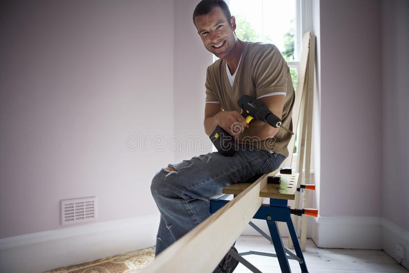 Man doing DIY at home, sitting on work bench beside timber, holding power drill, smiling, portrait stock photo