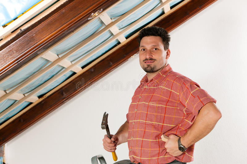 Man doing dry walling, working. Under a roof slope royalty free stock image