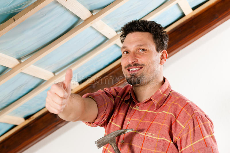 Man doing dry walling, working. Under a roof slope stock photos