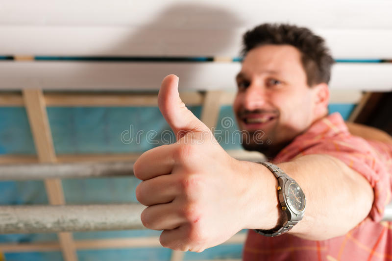 Man doing dry walling, working. Under a roof slope stock image