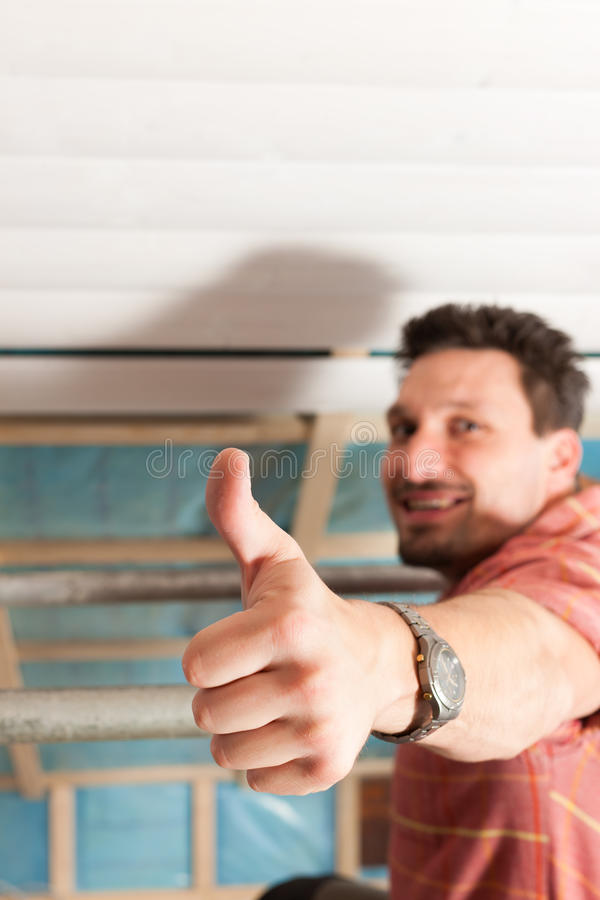 Man doing dry walling, working. Under a roof slope stock images