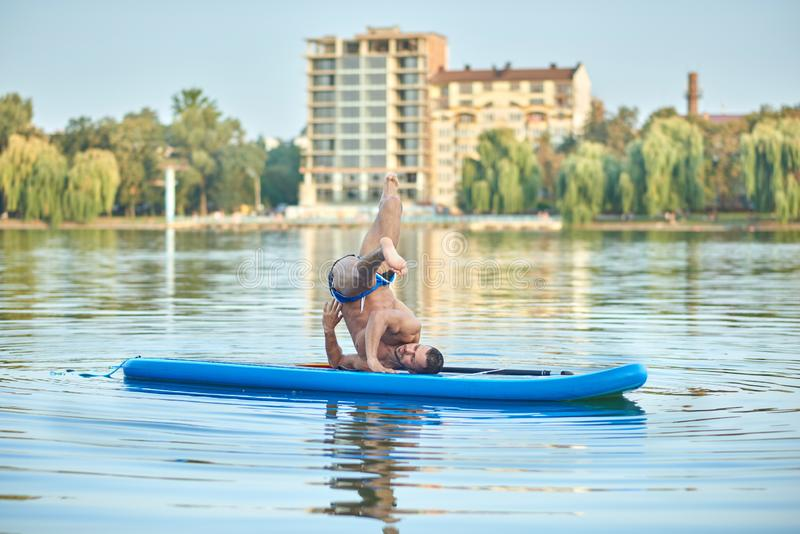 Man doing exercise difficult yoga pose on paddle board at daytime on lake. royalty free stock images