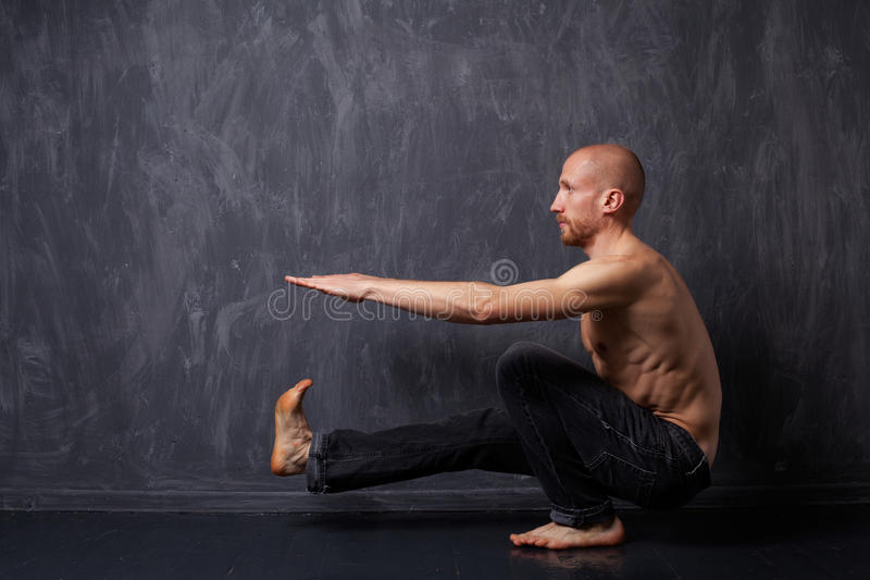 Man doing exercise. A man with a naked torso doing pistol squats on one leg on a dark background royalty free stock images