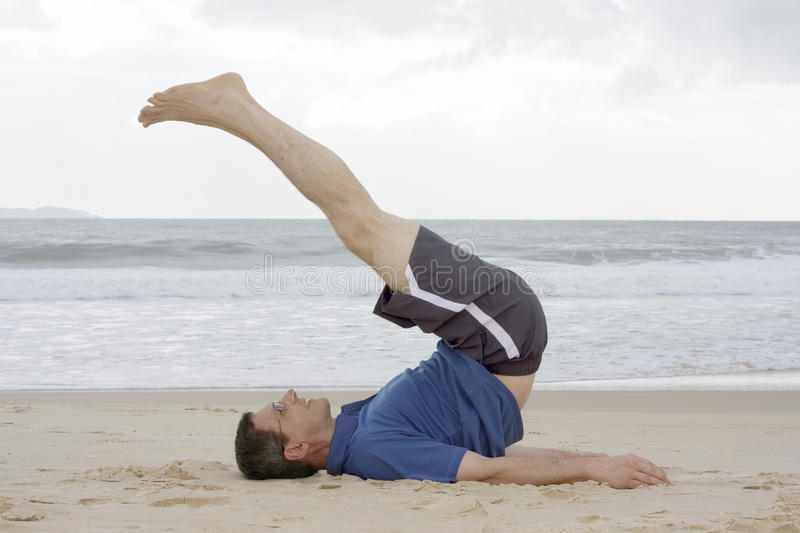 Man doing fitness exercises on a beach royalty free stock image