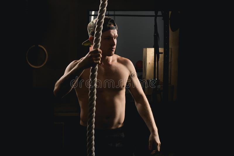 Athlete doing Fitness Rope Climb Exercise In Fitness Gym Workout. Man doing Fitness Rope Climb Exercise In Fitness Gym Workout stock photo