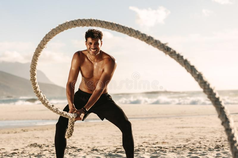 Man doing fitness training at the beach using battling rope royalty free stock photos