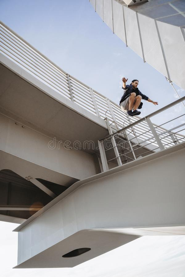 Man doing huge parkour jump from the bridge. Freerunning in the city royalty free stock image