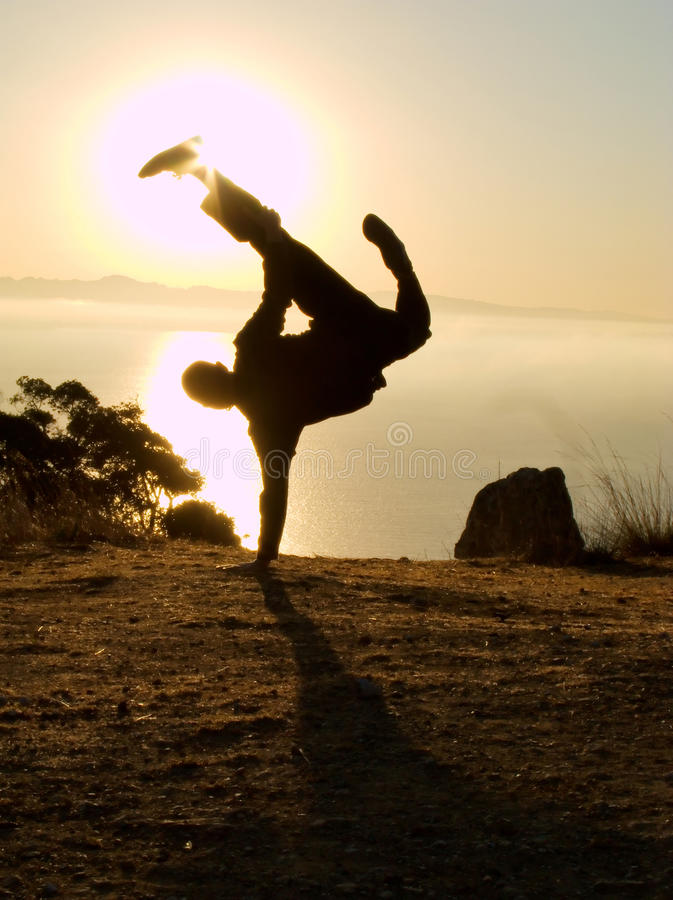 Man doing impressive one hand handstand at dawn stock images