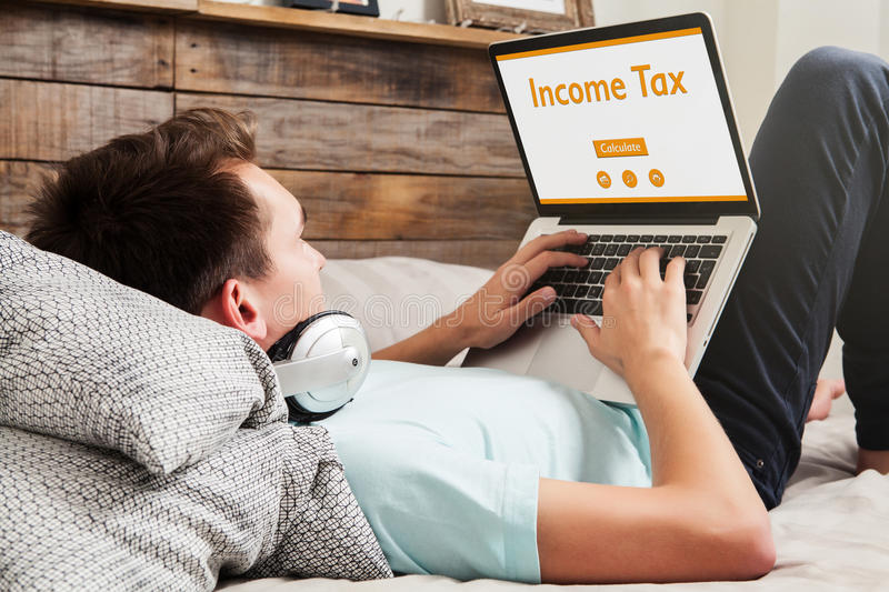 Man doing Income tax declaration on a website with a laptop at home. Freelance doing tax declaration through the internet stock images