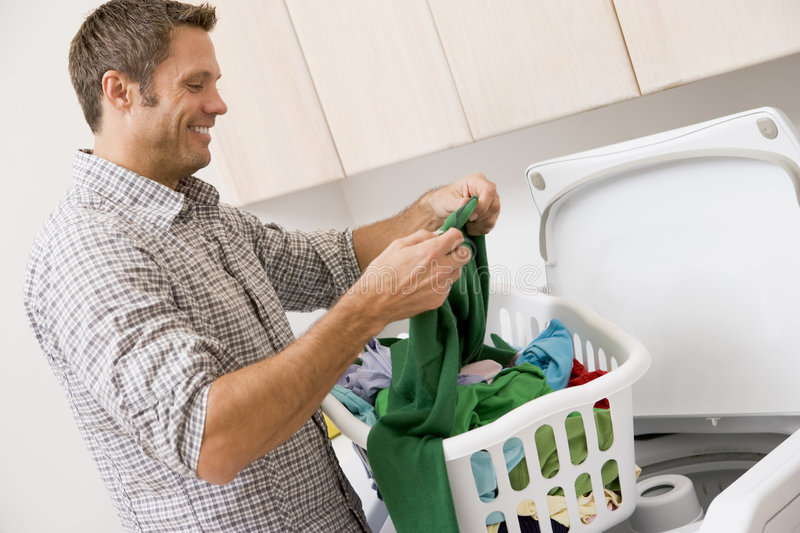 Man Doing Laundry. Looking At Label Smiling