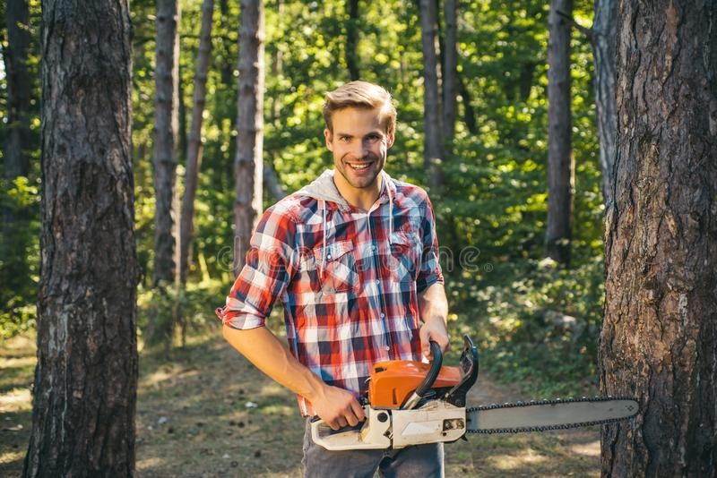 Man doing mans job. Happy Woodworkers lumberjack. Lumberjack with chainsaw on forest background. Agriculture and royalty free stock image
