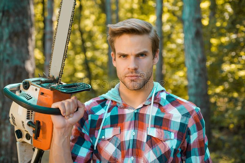 Man doing mans job. Lumberjack on serious face carries chainsaw. Deforestation is a major cause of land degradation and stock photos