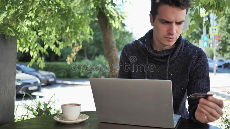Man Doing Online Shopping On Laptop Sitting in Cafe Terrace royalty free stock images