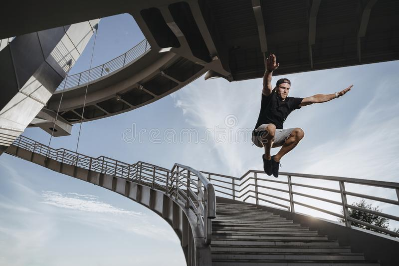 Man doing parkour in city. Freerun athlete performing massive jump royalty free stock image