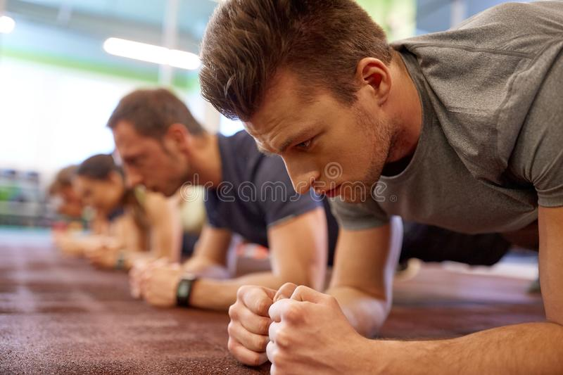 Man doing plank exercise at group training in gym. Fitness, sport, exercising and people concept - close up of men doing plank exercise at group training in gym royalty free stock photo