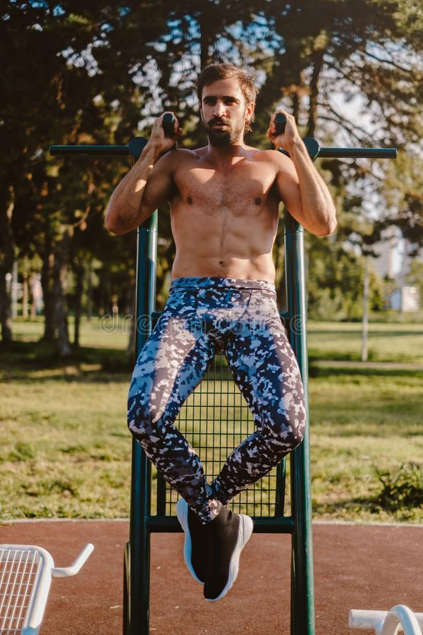 Man doing pull ups outside stock images