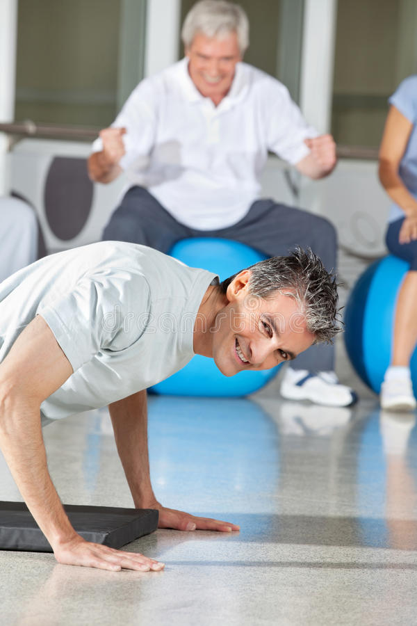 Man doing push ups in fitness. Smiling men doing push ups in fitness center on gym mat royalty free stock photography