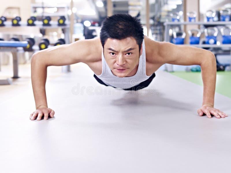 Man doing push-ups. On gym floor royalty free stock photo