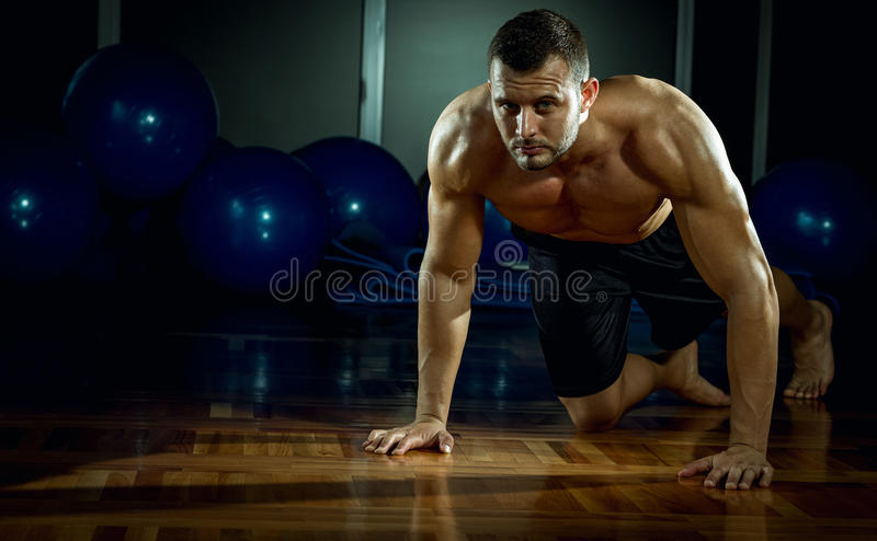 Man doing push-ups in gym stock photos