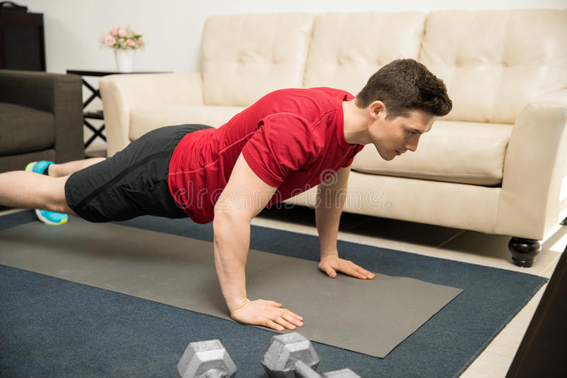 Man doing push ups at home. Strong and good looking young man doing push ups on an exercise mat at home stock image