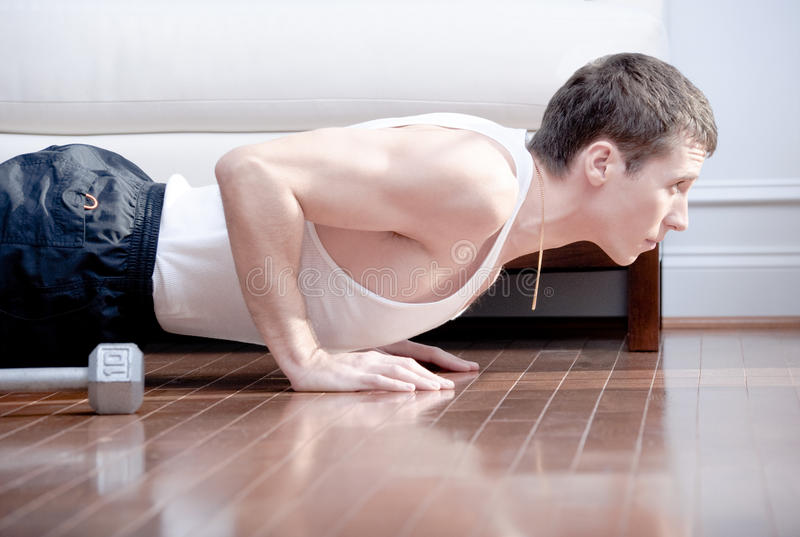 Man Doing Push-ups in Living Room stock photography