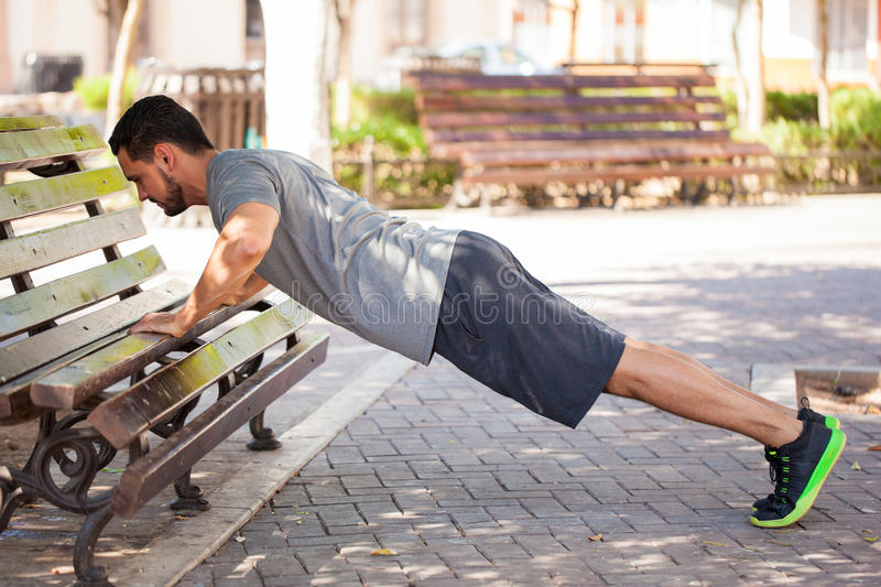 Man doing push ups outdoor in a park bench stock image