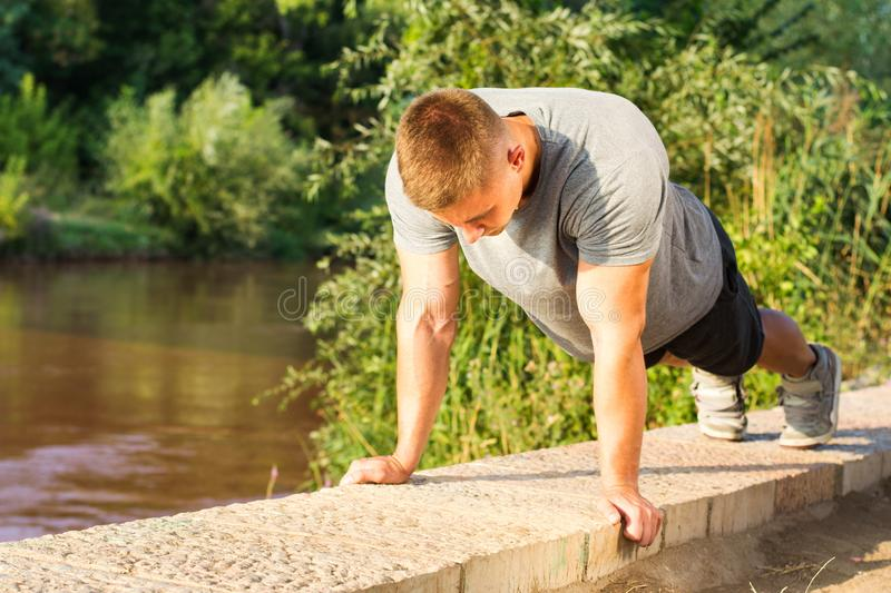 Man doing push ups by the river. Man performing push ups by the river stock image