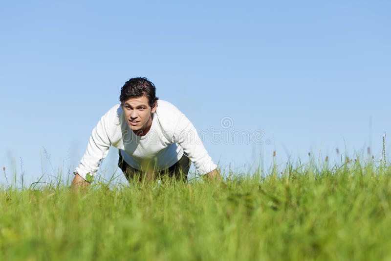 Man doing push ups in summer grass. Man doing push ups on a green meadow in summer, enjoying this exercise very much stock photography