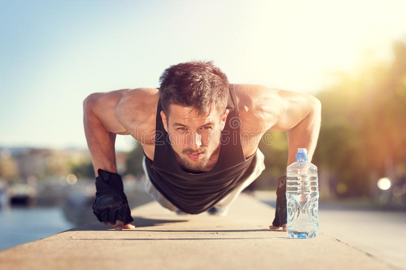 Man doing push-ups on sunny summer day. Muscular man doing push-ups outdoors on sunny summer day. Fitness and sport lifestyle concept royalty free stock photos