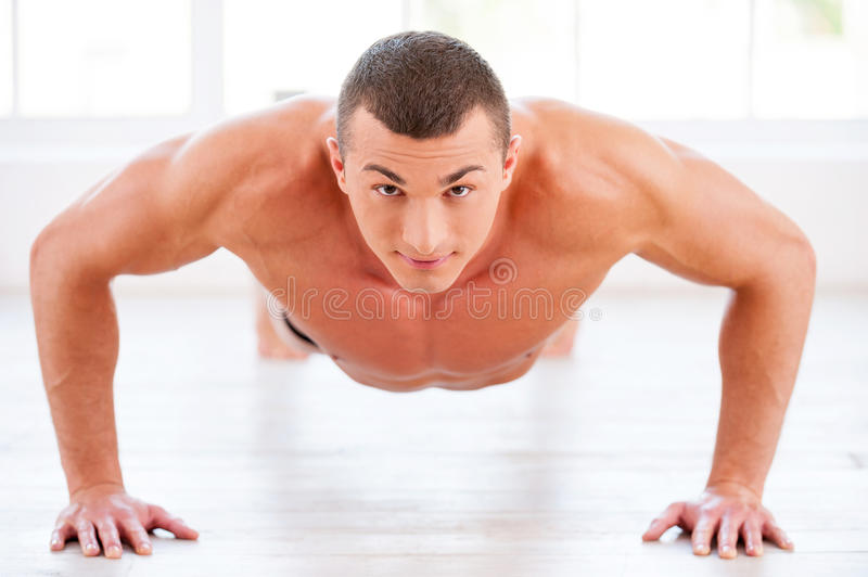 Man doing push-ups. Young muscular man doing push-ups and looking at camera stock photography