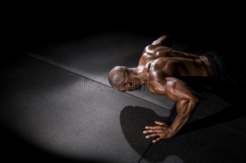 Man doing pushup. In dramatic lighting to show all his muscles stock photos